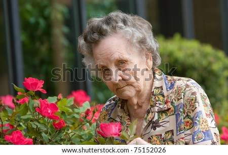 Elderly woman smelling flowers outside during spring - stock photo