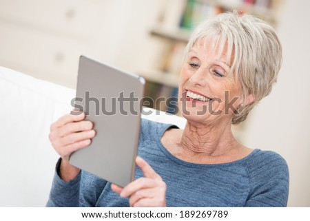 Elderly woman smiling happily as she reads the screen on her tablet computer checking on her social networking contacts - stock photo