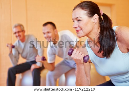 Elderly woman smiling with dumbbells in back training class in a fitness center - stock photo