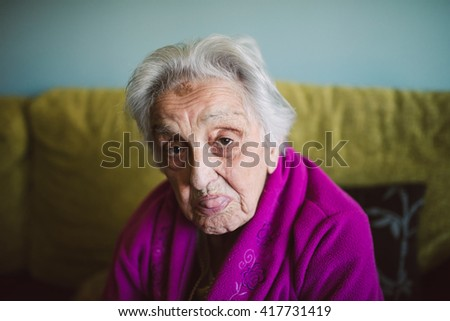 Elderly woman sticking out her tongue and looking at camera.