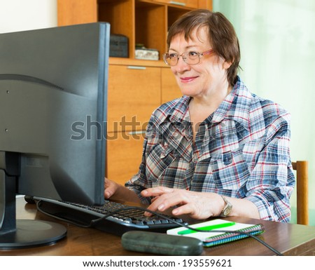 Elderly woman  studying computer literacy  in office interior - stock photo