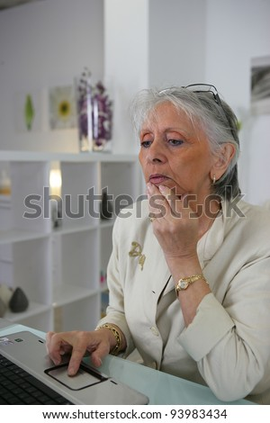 Elderly woman surfing the internet - stock photo