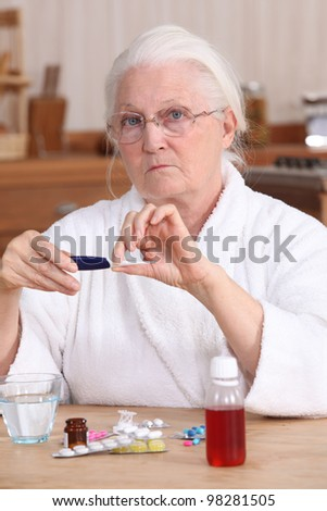 Elderly woman taking her medication - stock photo