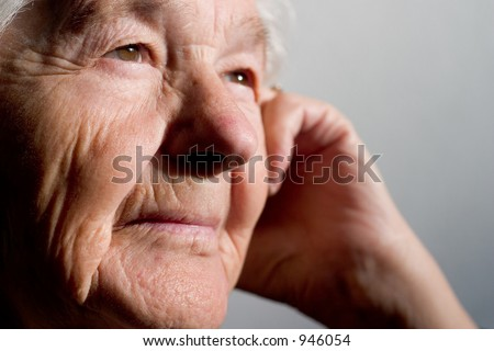 Elderly woman thinking. Focus on the first eye. - stock photo