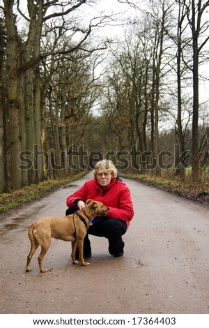 elderly woman together with the dog in a park