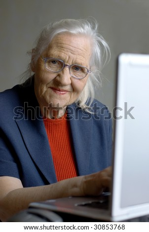 Elderly woman typing on laptop - stock photo