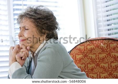 Elderly woman upset sitting alone by window with eyes shut - stock photo