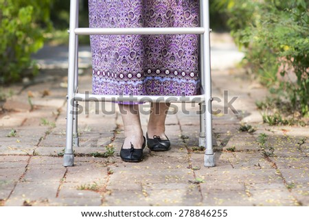 Elderly woman using a walker at home. - stock photo