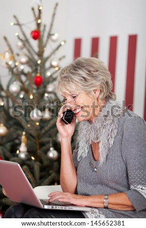 Elderly woman using telephone and her laptop computer on Christmas Eve to wish all her friends a Joyful Christmas, sitting in front of a red and white themed tree - stock photo