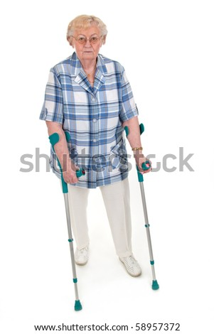 Elderly woman walking on crutches - isolated on white