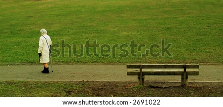 elderly woman walking through park - stock photo