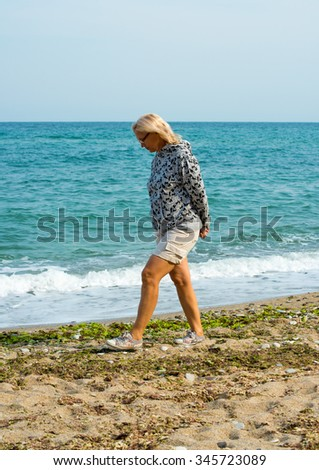 elderly woman walks on seeshore - stock photo
