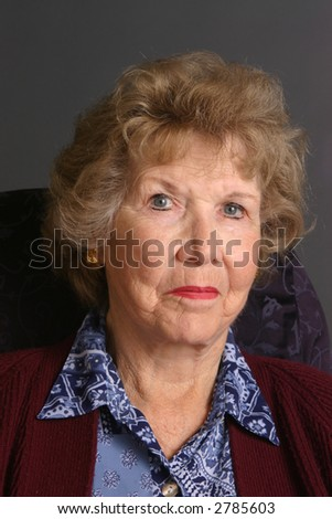 Elderly woman wearing blue dress and red sweater before dark background