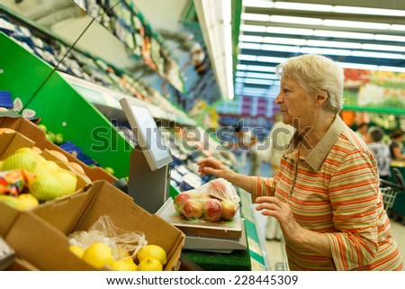 Elderly woman weighing goods on digital weight in supermarket, shopping for fruits and vegetables in produce department of a grocery store/supermarket (color toned image) - stock photo
