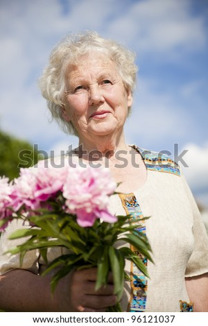elderly woman with a bouquet of flowers in the garden - stock photo