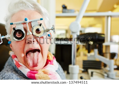Elderly woman with a trial frame sticking out tongue at the optician - stock photo