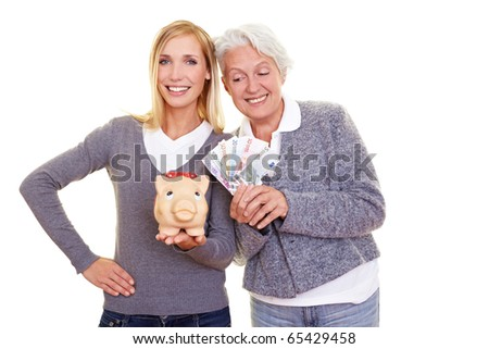 Elderly woman with banknotes looking over to young woman with piggy bank - stock photo