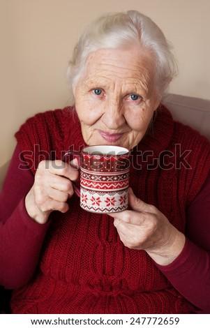 Elderly woman with cup of hot tea , winter season - stock photo