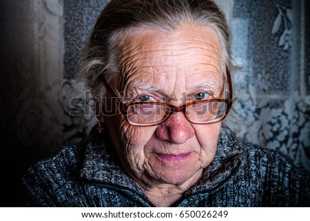 Elderly woman with glasses in rustic interior. Toned.
