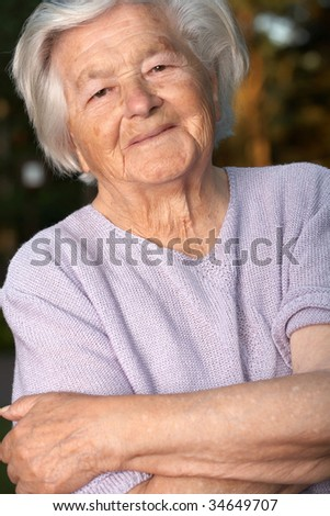 Elderly woman with hands crossed.
