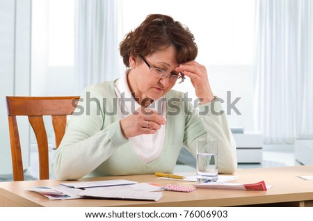 Elderly woman with headache worry about bill notice. - stock photo