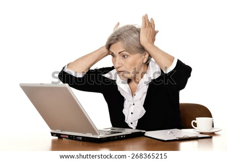Elderly woman with headset working on laptop isolated against white background