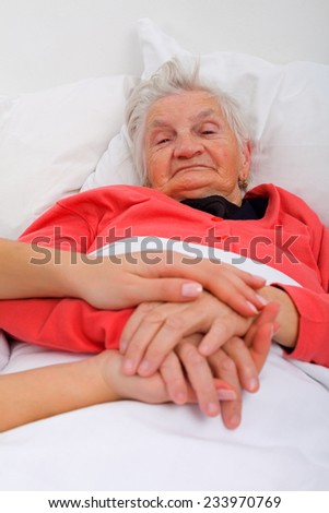 Elderly woman with her caregiver at home - stock photo