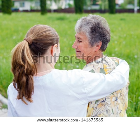 Elderly woman with her caretaker in the nature - stock photo