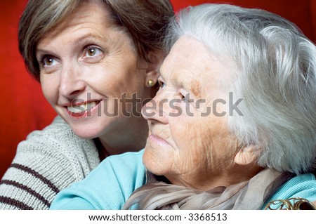 Elderly woman with her daughter. Focus on the elderly woman.