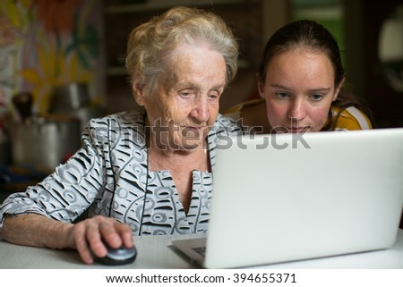 Elderly woman with her granddaughter working on laptop. - stock photo
