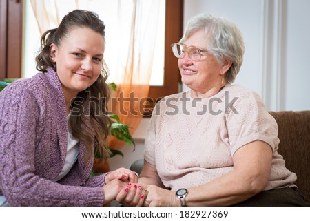 Elderly woman with her home caregiver - stock photo