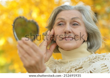 Elderly woman with mirror in autumn - stock photo
