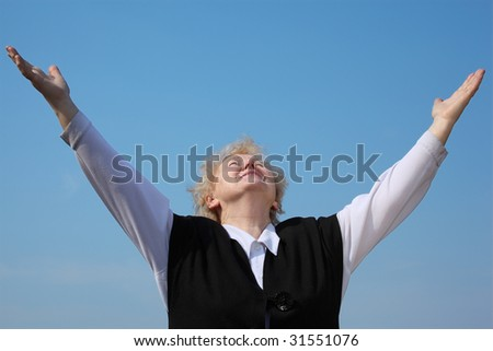 Elderly woman with raised hands looks in sky - stock photo