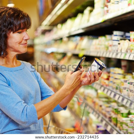 Elderly woman with smartphone scanning barcode of yogurt in a supermarket - stock photo