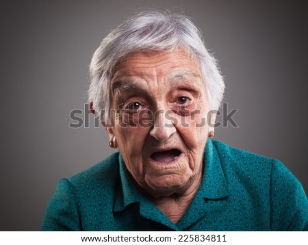 Elderly woman with surprised expression and isolated on dark background