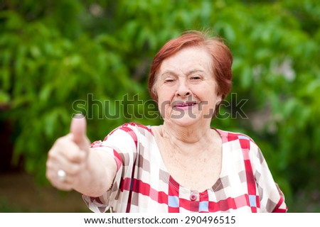 Elderly woman with thumb up laughing outdoors. Senior. Looking at camera. 70s. - stock photo