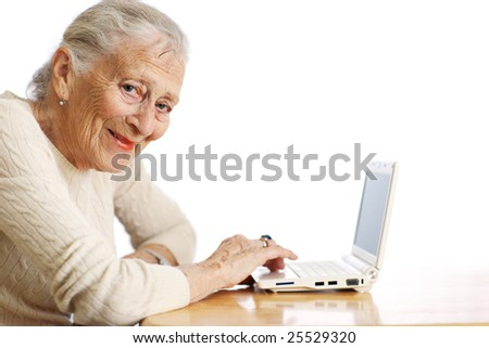 Elderly woman with ultra portable laptop computer. Shallow DOF. - stock photo