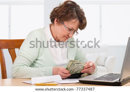 Elderly woman with wallet of money worry about bill notice. - stock photo