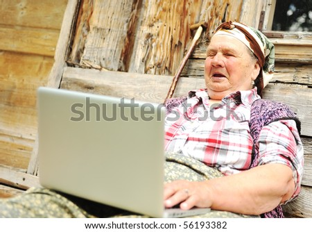 Elderly woman working on laptop in front of wooden house - stock photo
