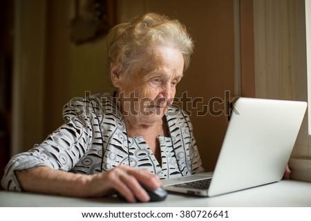 Elderly woman working on laptop sitting near the window.  - stock photo