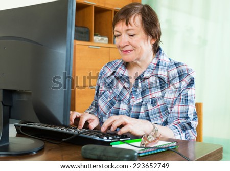 Elderly woman working with computer at the table - stock photo