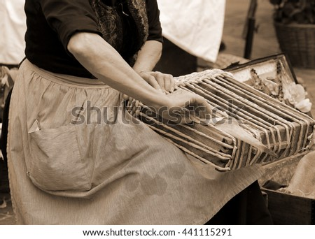 elderly woman working with her hands entwined the straw to create a beautiful handmade bag
