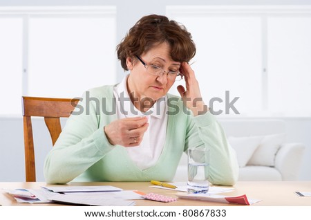 Elderly woman worry about bill notice - stock photo