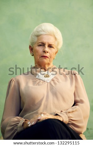 Elderly women and feelings, portrait of serious senior caucasian woman with severe look staring at camera on green background - stock photo