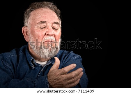 elderly, wrinkled man with painful look and hand reaching for help, isolated on black - stock photo