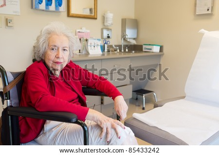 Elderly 80 year old woman with Alzheimer waiting for her doctor in the examination room.