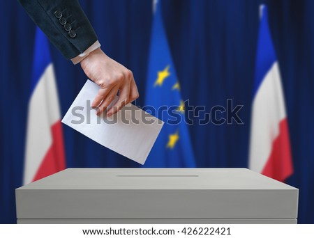Election in France. Voter holds envelope in hand above vote ballot. French and European Union flags in background. - stock photo