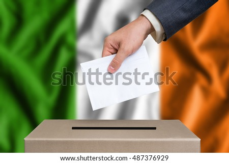 Election in Ireland. The hand of man putting his vote in the ballot box. Irish flag on background.