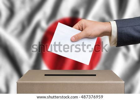 Election in Japan. The hand of man putting his vote in the ballot box. Japanese flag on background.