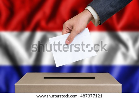 Election in Netherlands. The hand of man putting his vote in the ballot box. Dutch flag on background.